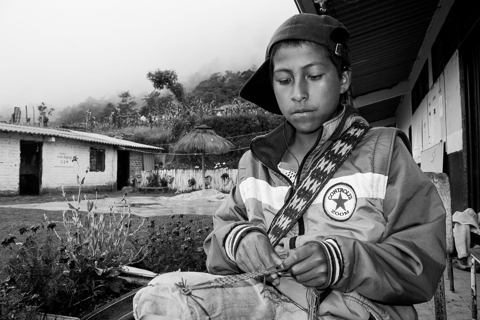 Fotografía de un joven artesano Nasa Yuwe tejiendo una manilla. Jambaló, Cauca