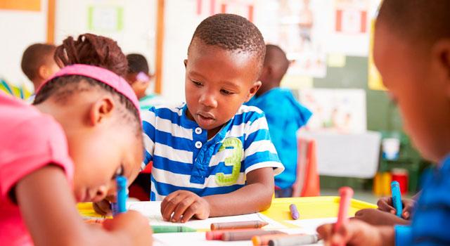 Niños en el aula de clase realizando tareas manuales con pintura y colores