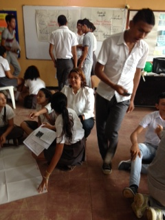 Profesora Dilia explicando a equipos sobre  trabajo en carteleras de paz