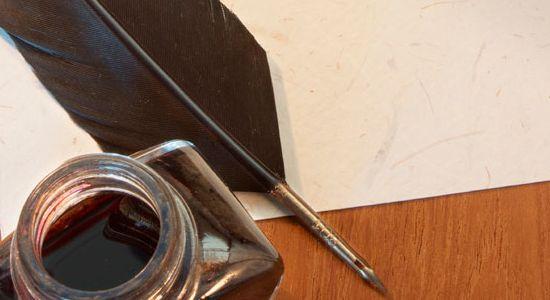 Pluma y tintilla junto a un pergamino