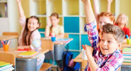 niños en un colegio participando en clase, muy felices
