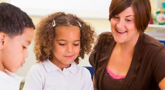 Dos niños recibiendo clase personalizada con su maestra