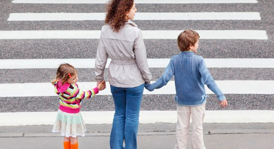 Familia tomada de la mano pasando calle por la sebra peatonal